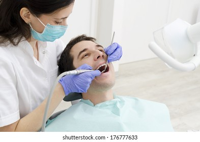 Young male with open mouth during oral checkup at the dentist