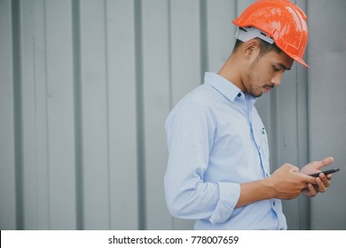 Young male in orange safety engineer helmet using cell phone or texting at the construction site.