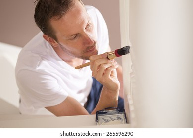 Young male painter painting indoor with paintbrush and white paint do it yourself