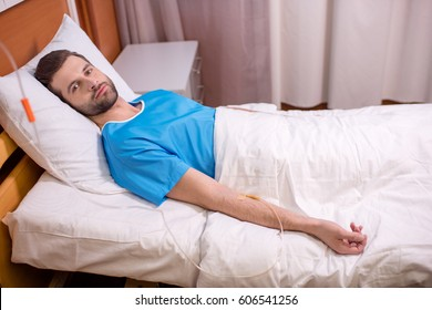 Young male patient lying in hospital bed with drop counter and looking at camera