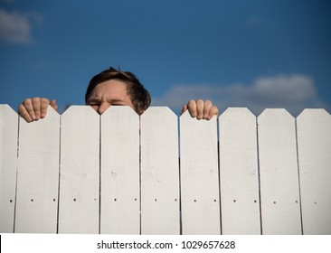 A young male person climbing a white fence