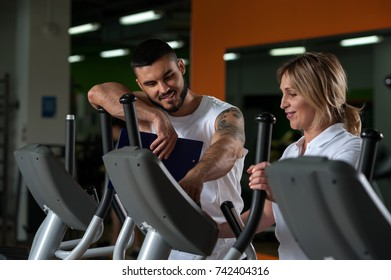 Young male personal trainer with female client in modern fitness center. Middle aged blonde woman working out on treadmill with the assistance of coach. Healthy lifestyle concept.