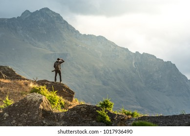 Young male photographer looking at mountain scenery during golden hour sunset in Queenstown, South Island, New Zealand. Travel and photography concept