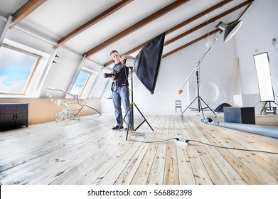 Young male photographer in professional studio adjusting equipment