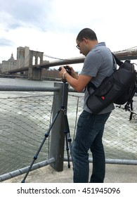 Young male photographer takes a time lapse photo of downtown Manhattan aside the Brooklyn bridge and East River