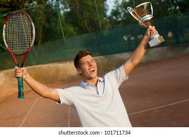 Young male player shouting happily with cup and tennis racket in hands.