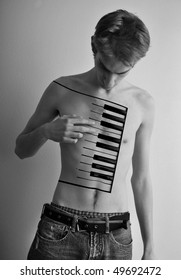 Young male playing a piano on his body. Black and white creative expressive portrait
