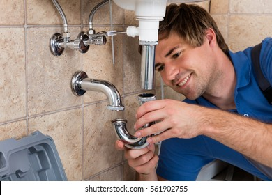 Young Male Plumber Fitting Sink Pipe In Bathroom