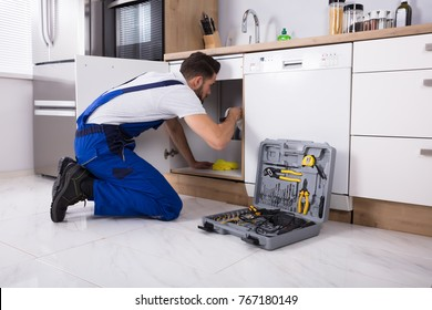 Young Male Plumber Repairing Sink Pipe In Kitchen