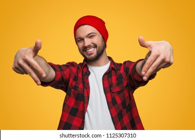Young male pointing with fingers down standing in studio with yellow background smiling and looking at camera