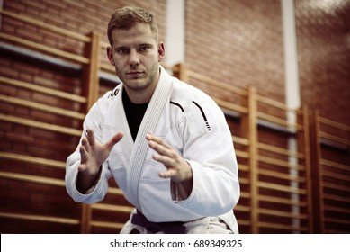 Young male practicing judo in kimono. Looking at camera.