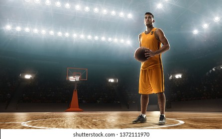 Young male professional basketbal player on floodlit professional sports arena with a ball