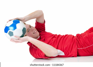 Young male red headed soccer, football player, studio shot, reflective surface