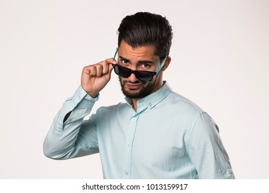 young male removing sunglasses
