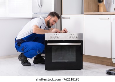 Young Male Repairman Repairing Oven In Kitchen