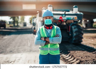 Young male road construction worker with face protective mask on his job. Bright sunny day. Strong light.