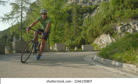Young male road cyclist pedalling up a steep asphalt road in the picturesque sunny woods in the lush green Slovenian mountains. Athletic Caucasian man training for a cyclocross race in the summer.