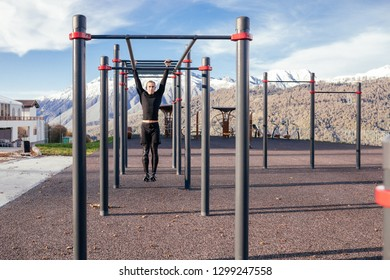 A young male runner doing pull ups on a horizontal bar on the street on a sunny warm day. Concept of calisthenic and sports training. Workout lifestyle concept