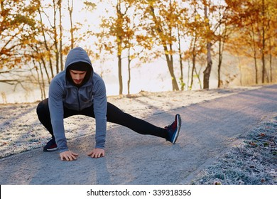 Young male runner stretching his legs after running workout