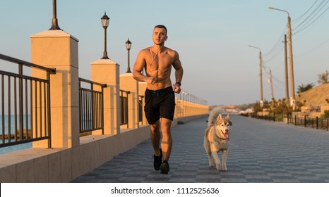 Young male running with siberian husky dog on the beach at sunrise, Running man. male runner jogging during the sunrise on beach. bodybuilder, athletic man