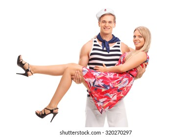 Young male sailor carrying his girlfriend in his arms and both looking at the camera isolated on white background