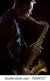 A young male saxophonist in a dark concert lit environment.