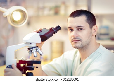 Young Male Scientist with Microscope - Portrait of a male doctor looking through a microscope in a laboratory