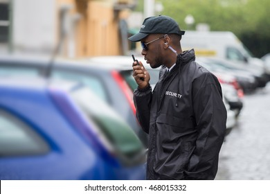 Young Male Security Guard In Black Uniform Using Walkie-Talkie On Street