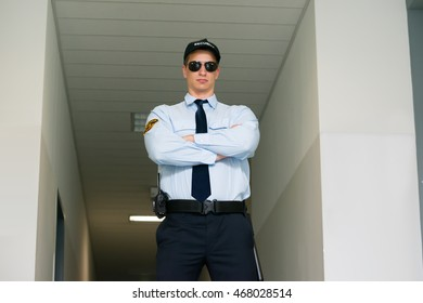 Young Male Security Guard Standing At The Entrance