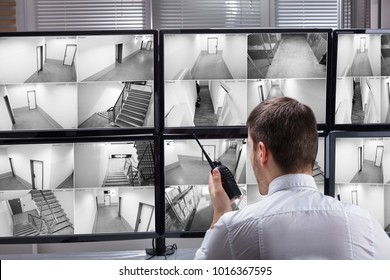 Young Male Security Guard Talking On Walkie-talkie While Monitoring Multiple CCTV Footage On Computer