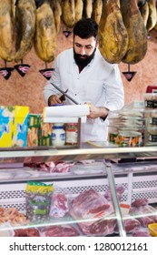 Young male seller offering displayed sorts of meat in butcher's shop