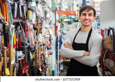 Young male seller posing at tooling section of household store