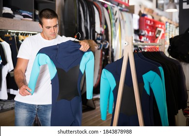 Young male shopper looking for new wetsuit during shopping in store