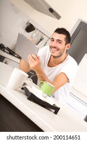 A young male sitting in the kitchen with a Tablet PC.