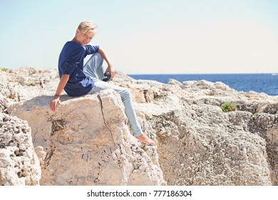 Young male sitting on textured rocks sea cliff holding binoculars contemplating the ocean, freedom adventure discovery holiday, looking outdoors. Healthy travel recreation lifestyle, enjoying nature.