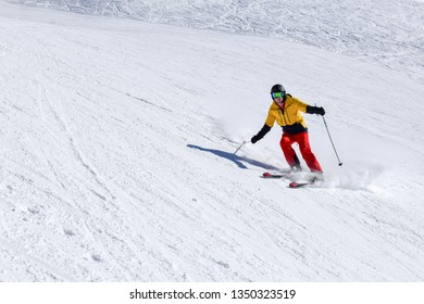 Young male skier in colorful outfit running down the slope in French Alpine mountains. Snowy landscape on sunny day during winter season