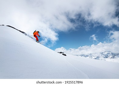 Young male skier in an orange suit rushes at speed along a snowy slope against the backdrop of high snow-capped mountains