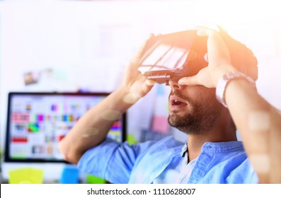 Young male software programmer testing a new app with 3d virtual reality glasses in office