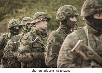 Young male soldiers in battle uniforms exercising outdoor