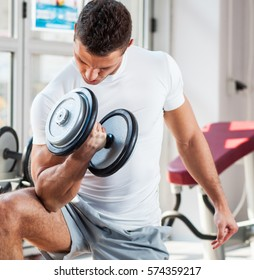 Young male with sport body doing workout at the gym.He lifting dumbbells.