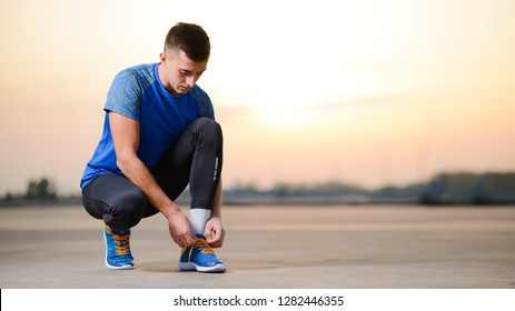 Young Male Sportsman Tying Running Shoes and Preparing for Urban Run at Sunset. Healthy Lifestyle and Active Sport Concept.