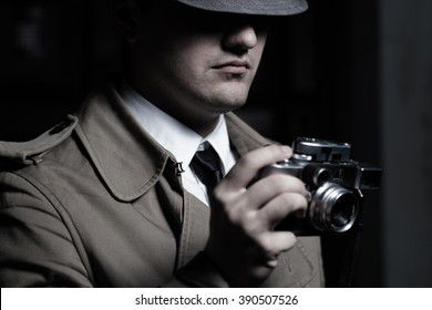 Young male spy agent wearing a hat, coat and a tie, holding rangefinder Leica film camera. Eyes hidden in the shadow.