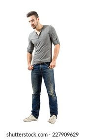 Young male standing looking down. Full body length portrait isolated over white background.