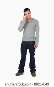 Young male standing while on the phone against a white background
