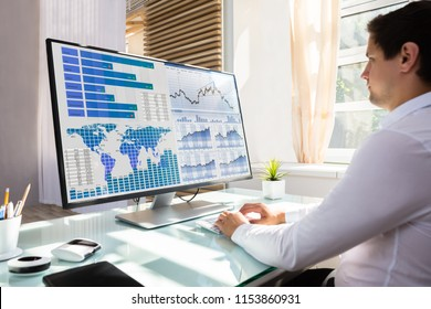 Young male stock market broker analyzing graph on computer at workplace