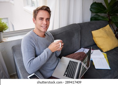 Young male student doing some work on his couch at home with his laptop and a cup of coffee