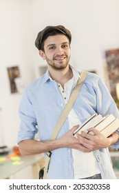 young male student with a pile of books in arms