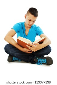 Young male student is sitting on the floor, reading a book. Isolated on a white background.