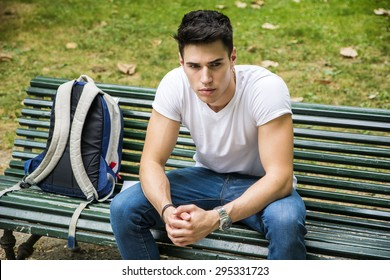 Young Male Student Sitting on the Bench in a Park, next to his Back Pack, While Thinking and Looking Away Seriously.