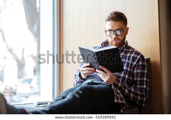図書館の窓台に座って本を読む若い男の生徒